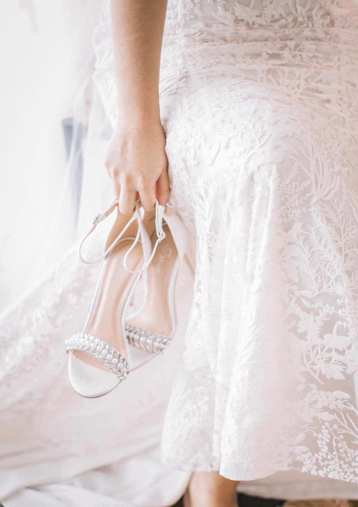 woman-in-white-gown-carrying-white-sandals